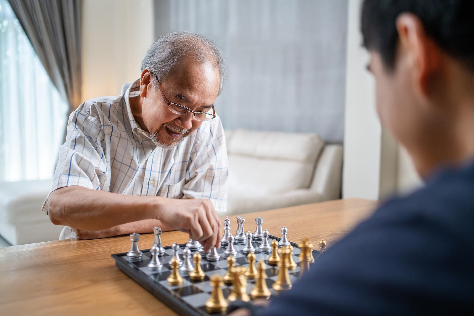 Asian Senior Elderly male spend leisure time, stay home after retirement. Happy smiling Old man enjoy activity in house playing chess game with friend together. Hospital Healthcare and medical concept