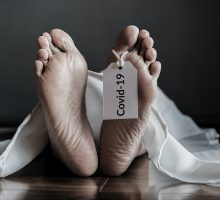 Dead body in morgue with a hanging COVID 19 tag hanging from toe
