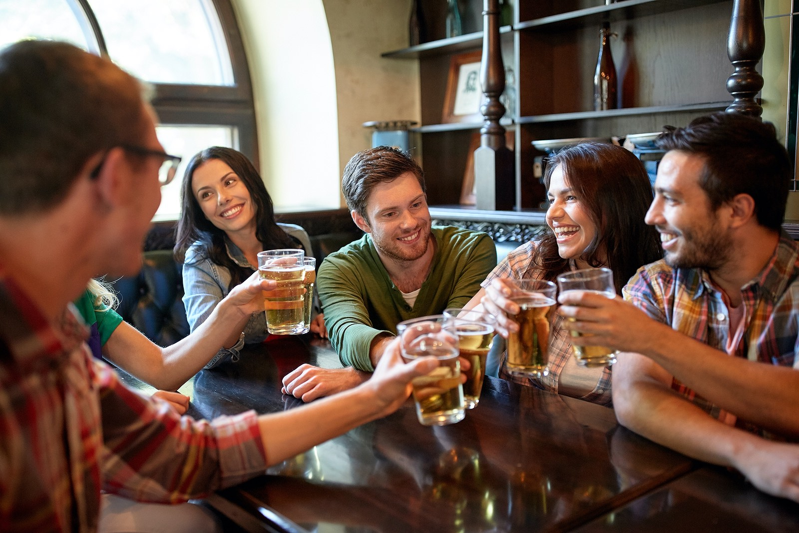 People, leisure, friendship and celebration concept – happy friends drinking draft beer and clinking glasses at bar or pub